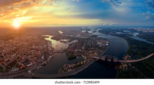Panoramic view of a modern city with a river. Skyline bird eye aerial view of the old part of the city - Podol district under dramatic cloud sunset sky. Rybalsky Island. Kiev. Ukraine