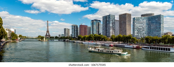 Panoramic view of modern district placed on embankment of Sena river in old Paris city against blue sky
