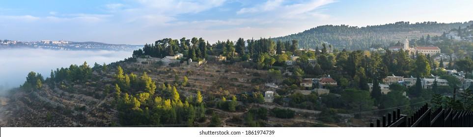 Panoramic view of morning mist and green Judean hills around Ein Kerem neighborhood - biblical birth place of John the Baptist, with Catholic Church of Saint John the Baptist; Jerusalem Israel