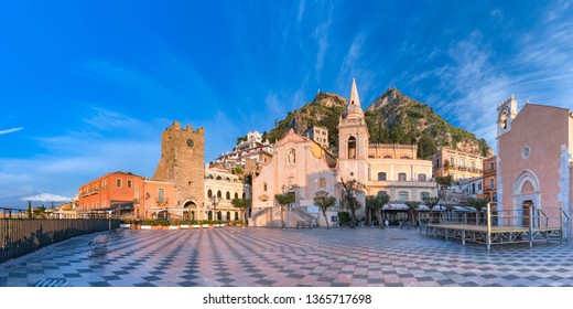 Panoramic view of the morning square Piazza IX Aprile with San Giuseppe church, the Clock Tower and Mount Etna Volcano on background, Taormina, Sicily, Italy