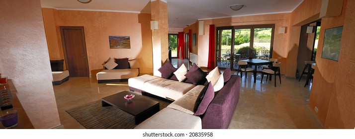 Panoramic view in a motel lobby with modern sofa and table