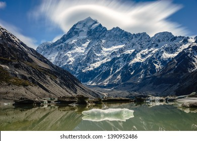 Panoramic view of Mount Cook and the surrounding Hooker Lake with clouds forming around the mountain's peak. Hooker Glacier can be seen in the background. Aoraki/Mount Cook National Park, New Zealand