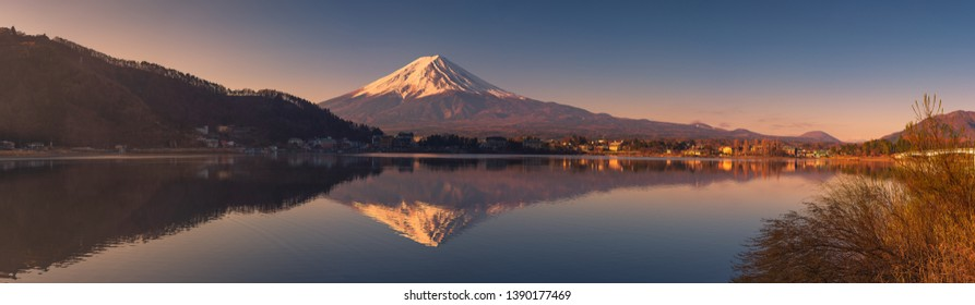 Panoramic view of Mount Fuji with beautiful golden light on the top and the reflection on the water during sunrise at Lake Kawaguchi, Yamanashi, Japan.