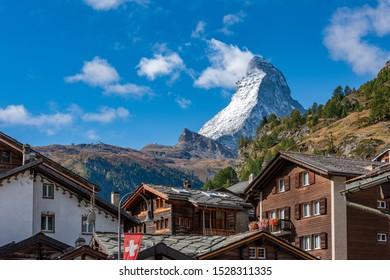 Panoramablick auf den Matterhorn mit den traditionellen Schweizer Chalets im Vordergrund während der Herbstsaison.