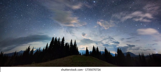Panoramic view of a mountain hill facing spruce forest and a mountain ridge, magical starry night sky with purple clouds above beautiful horizon, copy space. Concept of travelling, galaxy and nature. - Shutterstock ID 1735070726