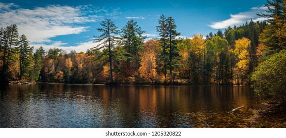 Panoramic view of Mountain Pond reflecting autumn colors in the Adirondacks, New York