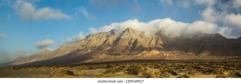 Panoramic view of mountain range with blue sky and big white clouds on Cofete beach, Fuerteventura, Spain.