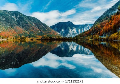 Panoramic view of the mountain village in the Austrian Alps. Autumn Landscape. Hallstatt, Austria. Blue sky and mountains. Beautiful and cozy town. Postcard concept. Hallstatter lake with reflections.