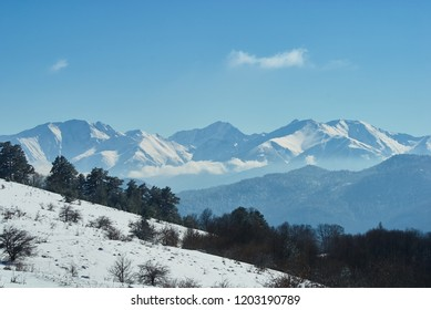 Panoramic view of the mountains. In the foreground there is a snow-covered glade, on the middle a forest, on the far a cliff, on the background a clear blue sky. Lago-Naki, The Main Caucasian Ridge