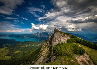 Panoramic view of mountains from Schafberg peak in Salzkammergut, Austria in a beautiful summer day with dramatic clouds and Attersee in the background