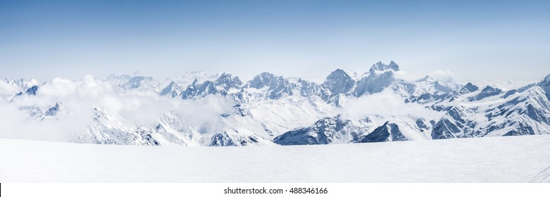 Panoramic view of a Mt. Elbrus ski slope and snowy Greater Caucasus mountains on the horizon at winter cold sunny day.