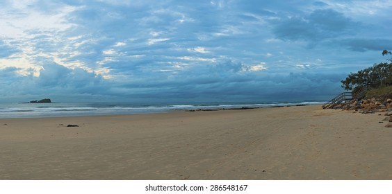 Panoramic view of Mudjimba beach Queensland, Sunshine coast, Australia. Evening shot with some storm clouds in the distance. Sandy beach foreground. Mudjimba or Old Woman island at left.