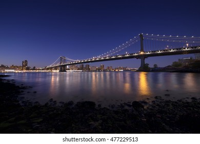 Panoramic view of New York City by night with Manhattan Bridge in the background, long exposure photography