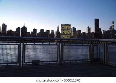 Panoramic view of the New York City Manhattan skyline at dusk.  Blue skies behind cityscape background as building lights turn on in the city that never sleeps