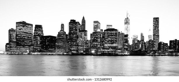 Panoramic view of New York Financial District and the Lower Manhattan at night viewed from the Brooklyn Bridge Park. High key black and white image.