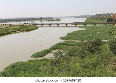Panoramic view of the Niger river in Niamey city, capital of Niger, West Africa. November, 10, 2019. Main bridge over the calm water with trees and vegetation at the foreground.