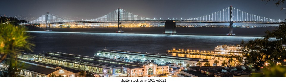 Panoramic view of the night illuminated Bay Bridge connecting San Francisco and Oakland; Ferry terminals and ptehr piers in the foreground; night photography; San Francisco bay area, California