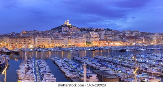 Panoramic view of night Old Port and the Basilica of Notre Dame de la Garde on the background, on the hill, Marseille, France
