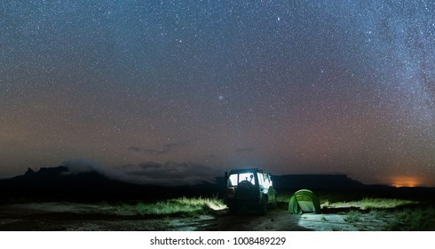 Panoramic view of the night sky with the Milky Way visible and some tepuis (table-top mountains) in the background. Taken on a camping site at Canaima National Park, in Venezuela.