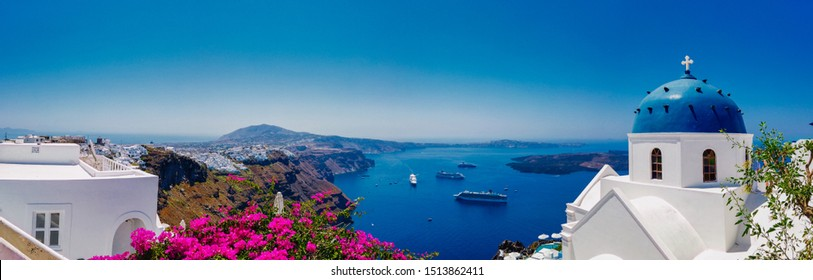 Panoramic view of Nikolaus monastery with domed cathedral and bell tower on seashore under blue sky in Santorini Greece