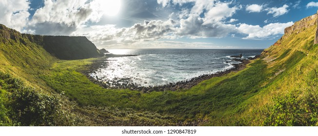 Panoramic view of the Northern Ireland shoreline. Breathtaking Irish landscape. The green grass covered lowland under the blue cloudy sky. Stunning bay with the boulders beach.