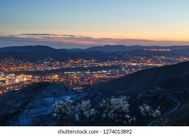 Panoramic view of Novorossiysk city and industrial zone Tsemdolina after sunset. Night cityscape view from Markotkh ridge, Russia