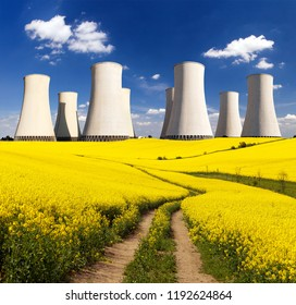Panoramic view of Nuclear power plant Jaslovske Bohunice with golden flowering field of rapeseed, canola or colza and rural road - Slovakia - two possibility for production of electric energy