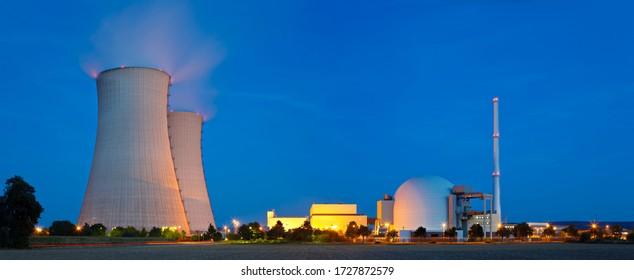 Panoramasicht auf ein Atomkraftwerk mit nachts blauem Himmel.