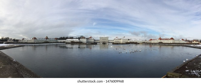 Panoramic view of Nymphenburg Palace in Munich, Germany during winter with lake and sky on background