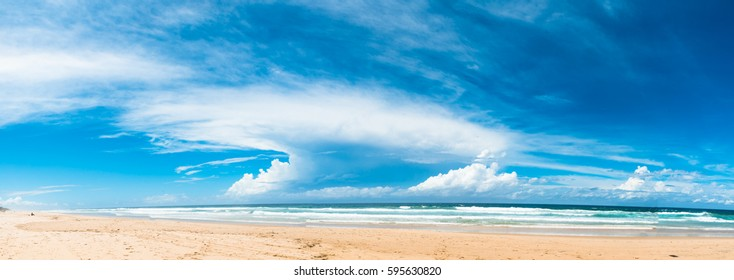 The panoramic view of the ocean beach with beautiful bright blue cloudy sky in Gold Coast, Australia