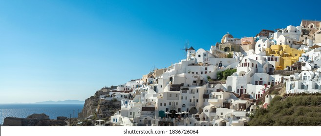 Panoramic view of Oia town in Santorini island with old whitewashed houses and traditional windmill, Greece Greek landscape on a sunny day