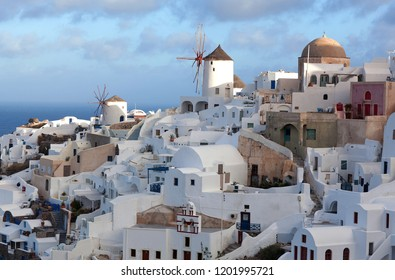 Panoramic view of Oia town at sunset, Santorini island, Cyclades, Greece. Traditional famous white houses, windmills and churches over the Caldera in Aegean sea.
