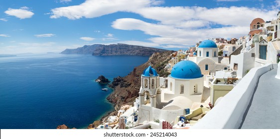 Panoramic view of the Oia village under puffy clouds, Santorini island, Greece