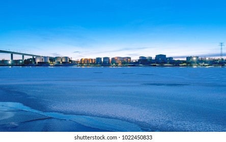 Panoramic view of an oil supply site during winter at the shore of an river with a bridge. Sodertalje, Sweden