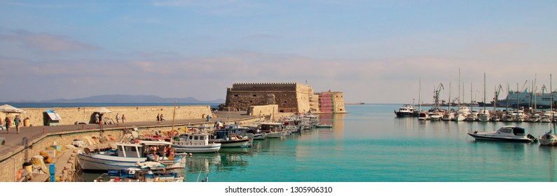 Panoramic view of the old bay with yachts and the old fortress, beautiful evening light, clear green sea, pink clouds