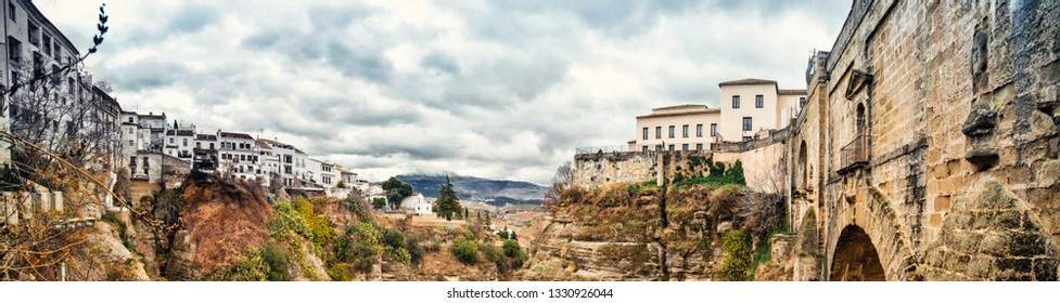 Panoramic view old city of Ronda and part of new bridge Puente Nuevo rises on the hug cliff, moody weather cloudy sky, picturesque famous white village in the  Province of Malaga, Andalusia, Spain