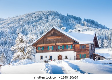 Panoramic view of old traditional farmhouse sitting on top of a hill in scenic winter wonderland scenery in the Alps on a beautiful sunny day with blue sky and clouds during Christmas time