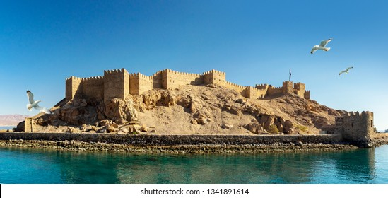 Panoramic view on ancient Fortress of Saladin on the Pharaoh Island in the Gulf of Aqaba and flying seagulls over the Red Sea. Old Castle of Sultan Salah ad-Din in Taba, travel on Sinai Peninsula.