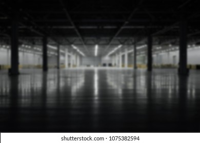 Panoramic view on blurred empty pavilion hall under construction, with dark front and light on the back wall, floor reflection. Interior metal construction. Blur effect