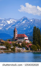 Panoramic view on the Brienz town on lake Brienz by Interlaken, Switzerland. Old fishing town with beautiful church and snow covered blue Alps mountains on background. Switzerland, Bohemia, Europe.