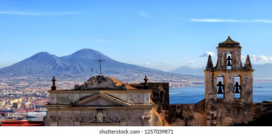 Panoramic view on the city of Naples with the harbor, sunset in autumn, in the background the volcano Vesuvius, italy