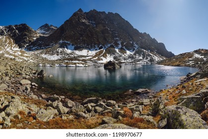 Panoramic view on Crystal mountain lake landscape with snowy peaks on background, Slovakia.