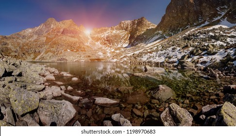 Panoramic view on Crystal mountain lake landscape with snowy Rysy peaks on background at sunset, Slovakia.