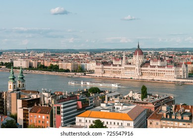 Panoramic view on the Hungarian Parliament Building on the bank of the Danube in Budapest. Sunny evening with clouds