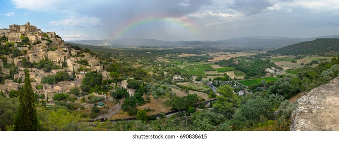 """Panoramic view on Luberon valley with rainbow on horizon. Old picturesque french town of Gordes with ancient castle """"Castrum Gordone"""" on the top. Famous landmarks in southeastern of France."""