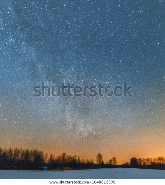 Panoramic view on the Milky Way above winter snowy field with forest and sawed logs at the background