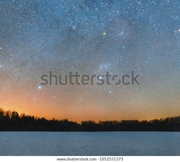 Panoramic view on the Milky Way and winter constellations with a hydrogen nebulas above winter snowy field with forest and light pollution shining at the background