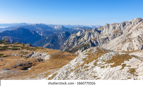 Panoramic view on mountains in Hochschwab region, Austrian Alps. The flora overgrowing slopes is golden. Autumn vibes in the mountains. Endless mountain chains shrouded in fog. Freedom and wilderness