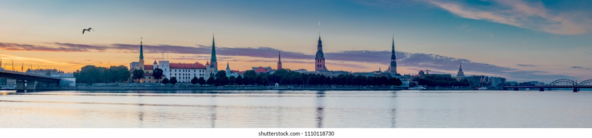 Panoramic view on old Riga city from left bank of Daugava river. Riga is the capital of Latvia and famous Baltic city widely known among tourists due to its unique medieval and Gothic architecture