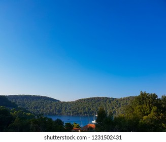 Panoramic view on the quit bay of the island Mljet, some boats at the harbor during the sunny day, mediterranean forest around
